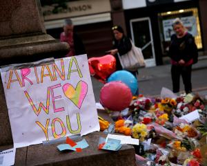 People look at flowers for the victims of the Manchester Arena attack. Photo: Reuters