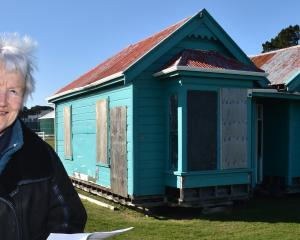 Heritage campaigner Ann Barsby stands next to the 19th-century Dunedin worker's cottage that she...