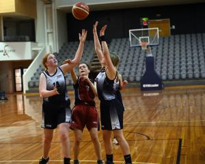 Kavanagh College Junior A player Abby Simpson (centre) tussles with Otago Girls High School...