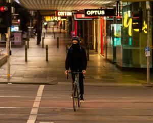 A cyclist crosses a usually busy Bourke St in Melbourne early today. Photo: Getty