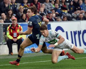 Highlanders winger Josh McKay gets to the ball just ahead of Blues first five-eighth Beauden...