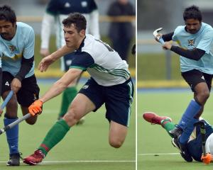 University Blue Whales player Davanand Bhikha (left) and Kings United's Zach Mason fight for the...