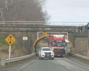 The stock truck is stuck under the railway overbridge. Photo: Mike Sheehan