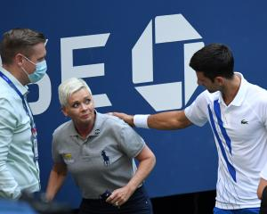 An apologetic Novak Djokovic (right) and a tournament official tend to a lineswoman struck with a...