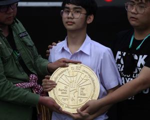 "Student leaders with a plaque declaring ""This country belongs to the people"" during a mass rally..."