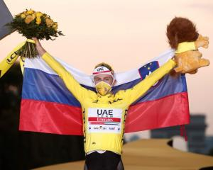Tadej Pogacar celebrates his victory on the podium. Photo: Reuters
