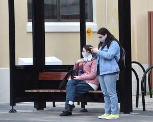 Two people wear face masks while waiting for a bus at the Dunedin bus hub yesterday. PHOTO:...