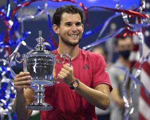 Dominic Thiem of Austria celebrates with the championship trophy after his match against...