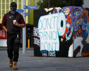 A man in a mask walks past street art in Prahran, in Melbourne. Photo: Getty