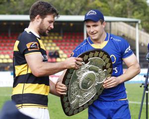 Taranaki captain Lachlan Boshier hands over the Shield to his Otago counterpart Michael Collins....