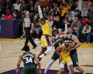 LeBron James rises for a slam dunk for the Los Angeles Lakers against Milwaukee Bucks prior to...