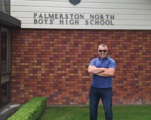 Matt Ratana posing outside his old school in a photo taken in 2017. Photo / Facebook via NZ Herald