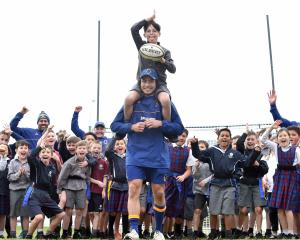 Josh Thompson (10), of St Bernadette's School, is carried on the shoulders of Otago midfielder...