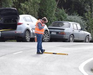 An investigator takes measurements at the scene of a fatal crash in Ravensbourne Rd, Dunedin,...