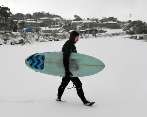 Kaka Point resident Hayden Campbell has the beach and waves to himself as he heads out for a surf...