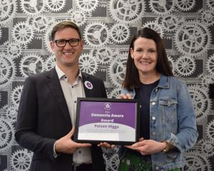 Alzheimers Otago manager Liz Harburg gives Polson Higgs partner Jamie Reidie a certificate for...