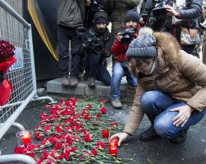 A woman lays flowers and candles and gather in front of the entrance of the Reina nightclub,...