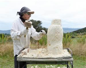 "Moira Crossman working Oamaru Stone to create ""Kahu""."