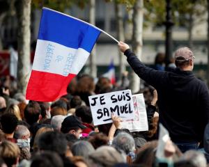 People gather at the Place de la Republique in Paris to pay tribute to Samuel Paty. Photo: Reuters