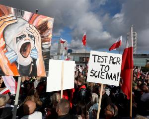 Demonstrators in Warsaw protest against restrictions announced by the government to prevent the...