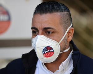"A man wears an ""I Voted"" sticker on his mask after voting in the US presidential election in Los..."