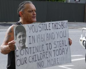 Alexandra man Tony Jarvis holds a placard outside the town's Oranga Tamariki office describing...