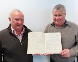 Former Fairton employees Jim Gordon (left) and Darcy Lysaght with the original minute book of the...
