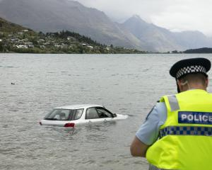 Police at Lake Wakatipu where a car was driven into the water. Photo: Matthew Mckew