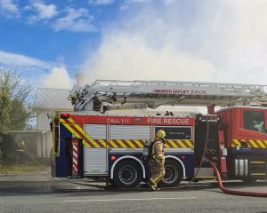 Smoke rises from a house in Ettrick St as firefighters respond to a blaze at the back of the...