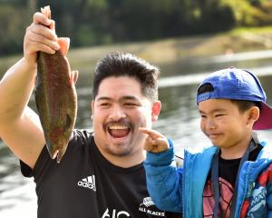 John and son Clyde Barcos celebrate after Clyde caught a rainbow trout on his first cast at the...