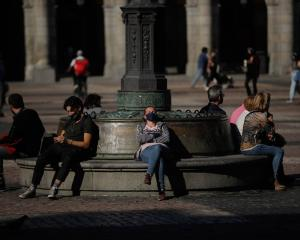 People wear face masks after the Spanish government imposed a 15-day state of emergency in the...