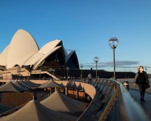 A woman in a mask walks through the Sydney Opera House forecourt back in August. There are...