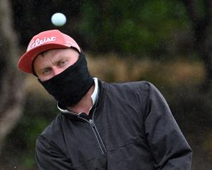 Ryan Bellamy, of Port Chalmers, pops up a bunker shot to ''gimme'' distance on the 4th green...