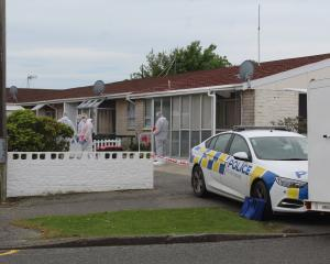 Police stand by as a scene examination is carried out on a Grace St property in Invercargill...