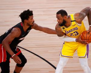 LeBron James is guarded by Jimmy Butler during yesterday's NBA Finals game in Orlando. Photo:...