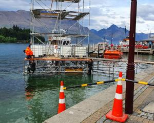 Workers in wetsuits set up a temporary structure at the Queenstown waterfront in 