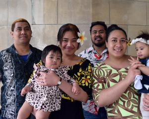 New citizens hug their daughters in the Dunedin Centre last week. They are friends Jackielynn...
