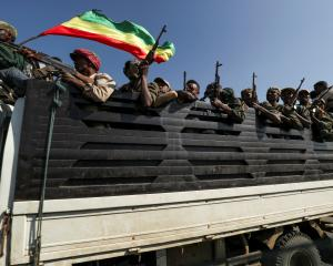 Members of Amhara region militias ride on their truck as they head to face the Tigray People's...