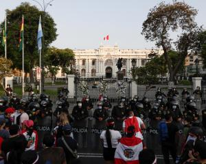 Police stand guard outside Congress after Peru's interim President Manuel Merino announced his...