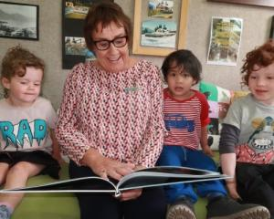 Retiring Wakatipu Kindergarten head teacher Sally Hogg reading to, from left, Stella Burrows, 3,...