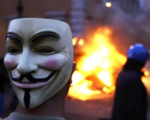 A protester wearing a Guy Fawkes mask look on as a Carabinieri police vehicle burns during a...