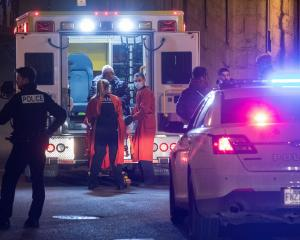 A person is treated by an ambulance crew in an area where multiple people were stabbed in Quebec...