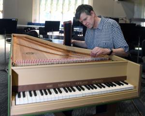 Dunedin City Choir musical director David Burchell fine-tunes the plucking mechanism of his...