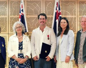 North Otago helicopter pilot Matt Irving (centre) with his Australian bravery award, presented by...