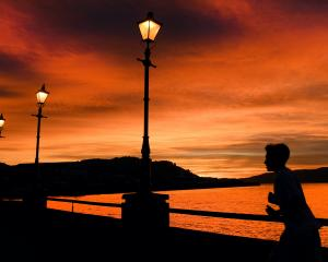 A runner jogs along the Steamer Basin in Dunedin as the sun rises. PHOTO: STEPHEN JAQUIERY