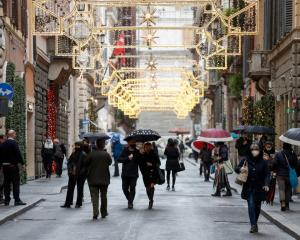 People wearing protective masks walk along Rome's Via dei Condotti on the day the Italian...