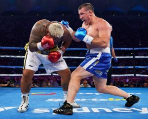 Paul Gallen (right) attacks against Mark Hunt during his upset boxing win last night. Photo:...
