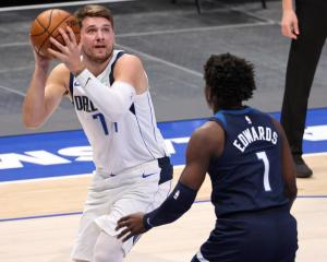 Dallas Mavericks' Luka Doncic  takes a shot against the Minnesota Timberwolves' Anthony Edwards...