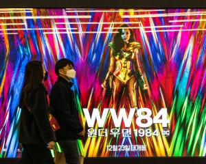 People wearing masks walk past an advertising billboard of the movie 'Wonder Woman 1984'. Photo:...