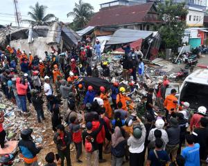Rescue workers carry a body containing an earthquake victim. Photo: Foto/Sigid Kurniawan/ via...